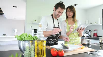 stock-footage-couple-in-home-kitchen-using-electronic-tablet
