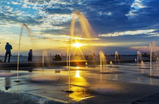 A gorgeous sunset in the city through the fountains.